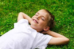 Smiling little boy lying in a field Stock Images