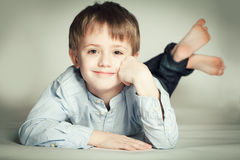Smiling little boy. Lying on the floor Stock Photo