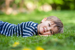 Smiling little boy lying on the grass in the park Stock Photography