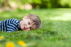 Smiling little boy, lying in the grass, smiling at the camera Royalty Free Stock Photography