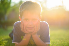 Smiling little boy lying in green grass Royalty Free Stock Photos