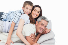 Smiling little boy lying on his parents on sofa Royalty Free Stock Photo