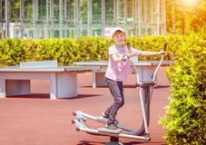 Smiling little boy on outdoor sport ground exercise at gym machine training feet and arms. Smiling little boy on outdoor sport ground exercise at gym machine royalty free stock photography
