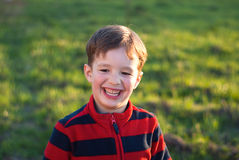 A smiling little boy outdoors. On grass background Stock Images