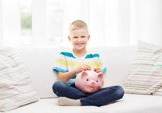 Smiling little boy with piggy bank and money Royalty Free Stock Photography