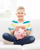 Smiling little boy with piggy bank and money Stock Image
