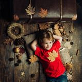 Smiling little boy playing with leaves. Smiling little boy wearing in fashionable seasonal clothes having Autumnal mood. Blonde little boy resting with leaf on stock images