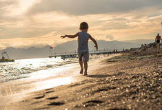 Smiling little boy playing in the sea on the sunset. Positive human emotions, feelings, joy. Portrait of happy little kid boy on t Stock Image