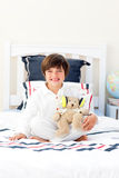 Smiling little boy playing with a teddy bear Royalty Free Stock Image