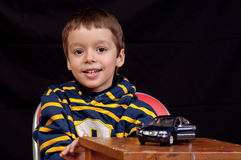 Smiling little boy plays with toy car Stock Photography