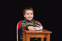 Smiling little boy plays with toy car Royalty Free Stock Photos
