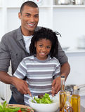 Smiling little boy preparing salad with his father Stock Photography