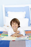 Smiling little boy reading in bed Royalty Free Stock Images