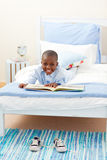 Smiling little boy reading a book Stock Image