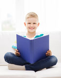 Smiling little boy reading book on couch Royalty Free Stock Photos