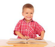 Smiling little boy reading book on the desk Royalty Free Stock Photos