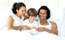 Smiling little boy reading with his parents Stock Photos