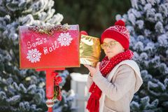 Smiling little boy with red hat and green glasses with his letter near the Santa`s mailbox royalty free stock photography