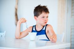 Smiling little boy refuses to eat delicious yogurt Stock Photography
