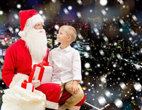 Smiling little boy with santa claus and gifts Royalty Free Stock Photography