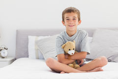 Smiling little boy sitting on bed holding his teddy bear Stock Photos