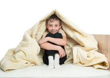 Smiling little boy sitting on a bed under a blanket and hugging her knees Royalty Free Stock Photos
