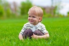 Smiling little boy sitting in fresh grass Stock Photo