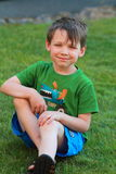 Smiling little boy sitting in the grass. A smiling little 5 yr old boy in green shirt and disheveled dark hair sitting in the grass. Shallow depth of field Royalty Free Stock Photo