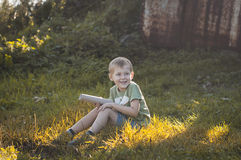 Smiling little boy sitting on grass Royalty Free Stock Photography