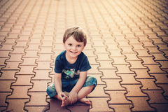 Smiling little boy sitting on the ground Royalty Free Stock Photography