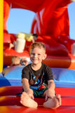 Smiling little boy sitting on a jumping castle. Smiling happy barefoot little boy sitting on a colorful inflatable plastic jumping castle at a fairground or kids Stock Image