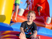 Smiling little boy sitting on a jumping castle. Smiling happy barefoot little boy sitting on a colorful inflatable plastic jumping castle at a fairground or kids Royalty Free Stock Photo