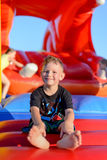 Smiling little boy sitting on a jumping castle. Smiling happy barefoot little boy sitting on a colorful inflatable plastic jumping castle at a fairground or kids Stock Photography