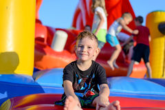 Smiling little boy sitting on a jumping castle. Smiling happy barefoot little boy sitting on a colorful inflatable plastic jumping castle at a fairground or kids Royalty Free Stock Photos