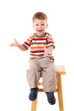Little boy sitting on stool. Smiling little boy sitting on stool, isolated on white Stock Photo