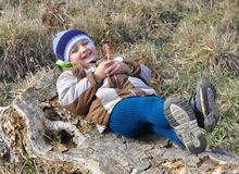 Smiling little boy sitting on a stump with candy Royalty Free Stock Photos
