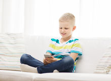 Smiling little boy with smartphone at home Stock Photos