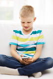 Smiling little boy with smartphone at home Royalty Free Stock Image