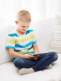 Smiling little boy with smartphone at home Stock Photography