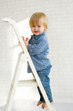 Smiling little boy standing on the step of a ladder Stock Photos