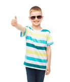 Smiling little boy in sunglasses showing thumbs up Stock Photo