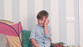 Smiling little boy talking on mobile phone in his room stock video