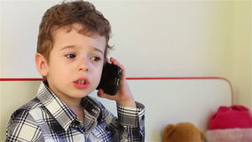 Smiling little boy talking on smartphone stock video footage