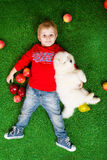 Smiling little boy three years old laying with white puppy Royalty Free Stock Image
