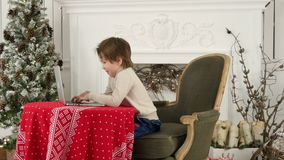 Smiling little boy typing letter to Santa Claus on a laptop near the Christmas tree stock video