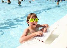 Smiling little boy using laptop in pool at resort Stock Image
