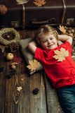Smiling little boy wearing in fashionable seasonal clothes having Autumnal mood. Blonde little boy resting with leaf on. Stomach lies on wooden floor in autumn stock image