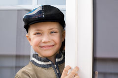 Smiling little boy at the window Stock Photos