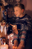 Smiling little boy on the window in Christmas time Stock Image