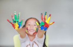 Smiling little cheerful girl showing her colorful hands and cheek painted in kids room. Focus at baby hands stock images
